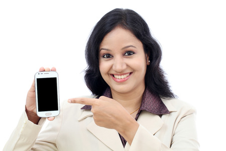 Young business woman showing with black display of mobile phone against white