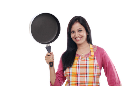 nonstick: Young Indian woman holding kitchen utensil against white background
