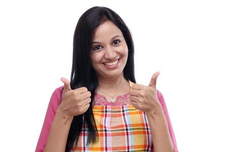 casalinga: Felice giovane donna indiana che indossa un grembiule da cucina e mostrando thumbs up Archivio Fotografico