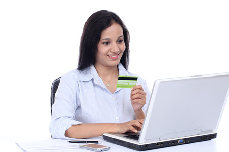 Happy young business woman doing online shopping against white Stock Photo