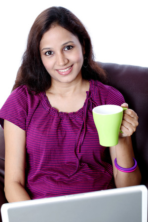 Young happy Indian woman drinking coffee while working on laptop  photo