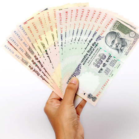 Hand holding Indain rupee notes on white background