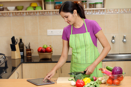Young Indian woman using a tablet computer in her kitchen  Banco de Imagens