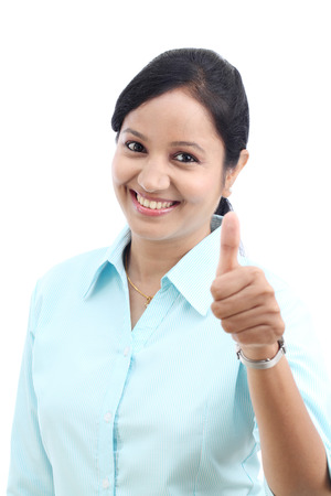 Young Indian business woman with thumbs up gesture against white Stock Photo