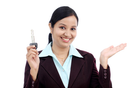 Happy young Indian business woman holding key against white background Stock Photo - 27755699