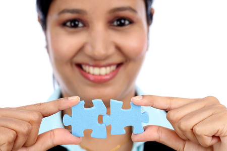 Young Indian business woman joining two jigsaw puzzle pieces against white background photo