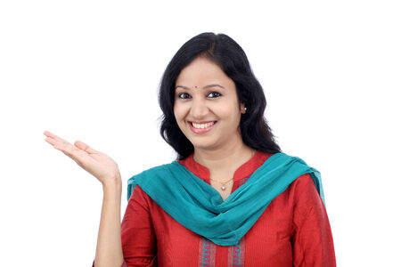 Happy young woman gesturing an open hand against white background photo