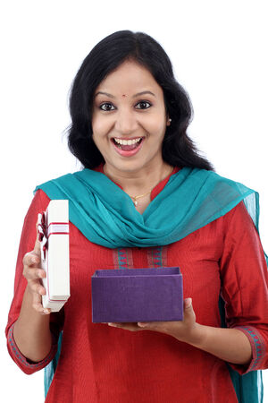 Surprised young woman with gift box against white background photo