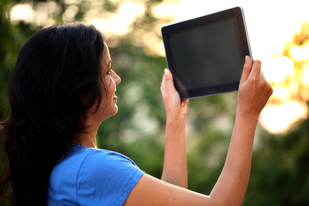 Young woman taking picture from tablet computer at outdoors photo