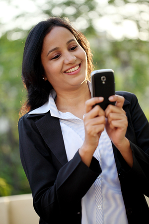 Happy young business woman text messaging at outdoors photo