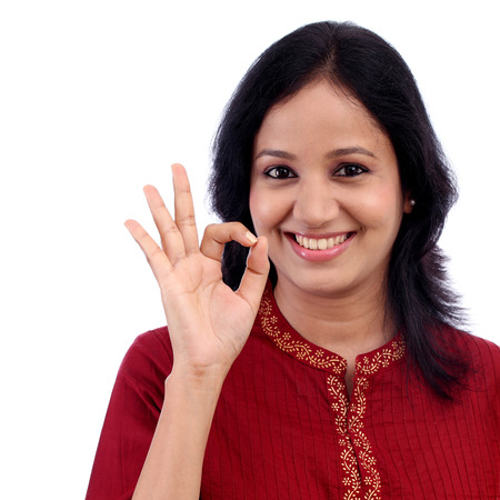 kameez: Happy young woman making OK sign against white background
