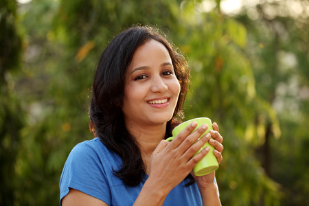 Young woman drinking coffee at outdoors photo
