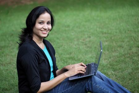 colegios: Joven estudiante feliz trabajando con el ordenador de la tablilla en el campus