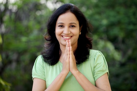 Happy young woman greeting with Namasthe gesture at outdoors photo