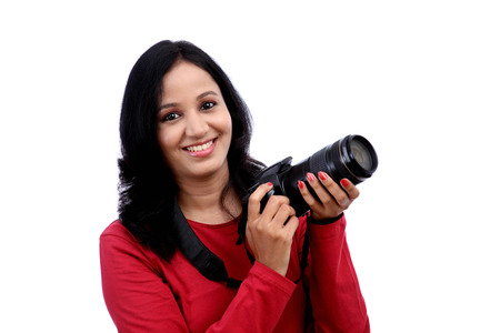 Young woman photographer with camera against white background photo