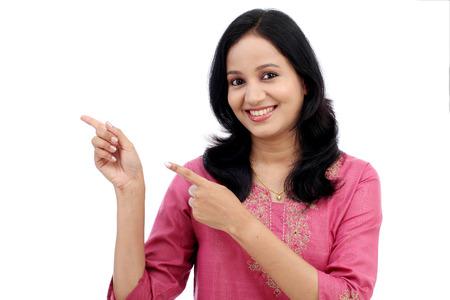 fille indienne: Sourire jeune femme montrant présentation isolé sur blanc Banque d'images