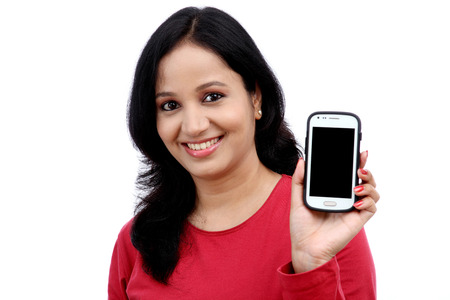 Beautiful young woman holding mobile phone against white background Imagens