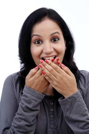 Young woman covering mouth with hands and laughing against white photo