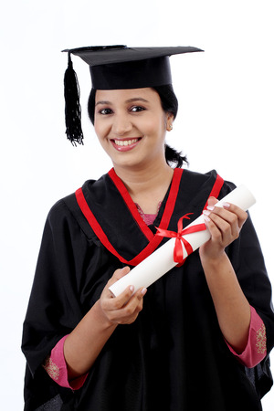 Happy young female student holding diploma against white background Banco de Imagens