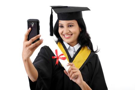 graduacion de universidad: Hembra joven estudiante graduada teniendo selfie Foto de archivo