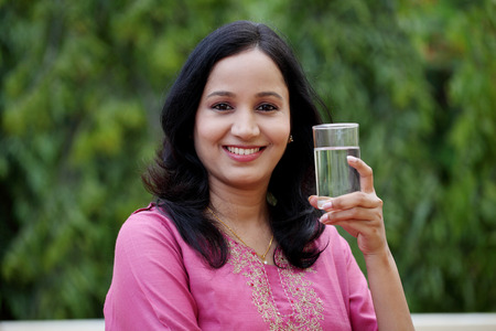 indian summer: Young woman drinking water