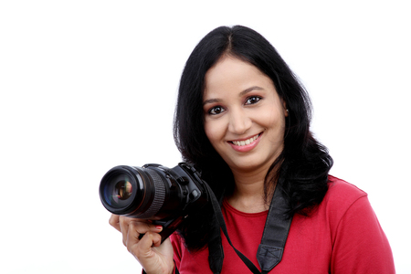 woman white background: Young woman photographer with camera against white background Stock Photo
