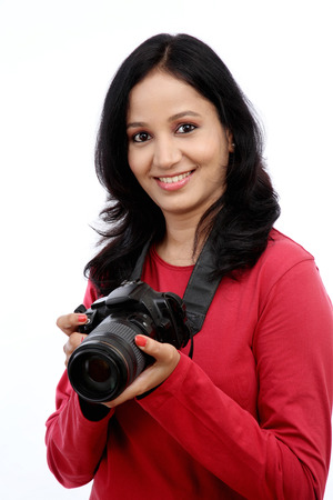 Young woman photographer with camera against white background Banco de Imagens