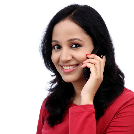 salwar: Happy young woman talking on mobile phone against white background Stock Photo