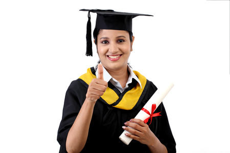 Smiling young graduation student making thumbsup gesture against white photo