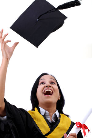 Happy young female graduate tossing up her hat against white photo