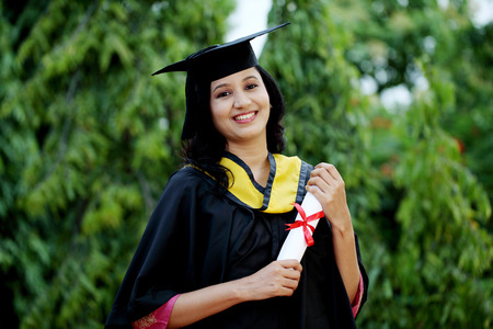 college graduation: Young female student with diploma at outdoors