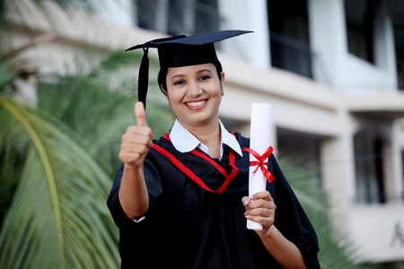 Young female student with diploma at outdoors photo