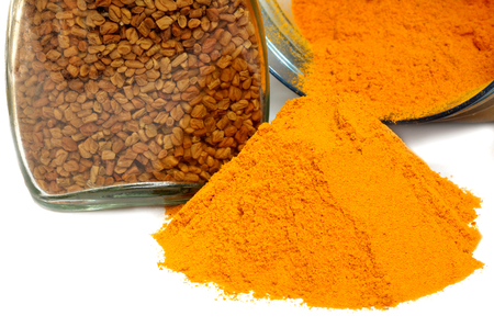 Fenugreek seeds and ground turmeric over white background Imagens