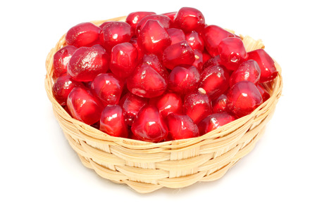 Red Pulp of pomegranate fruit on bamboo basket over white background