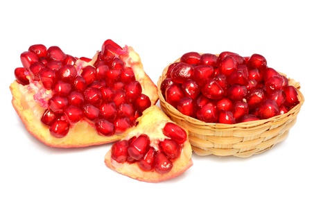 Red Pulp of slices pomegranate fruit on bamboo basket over white background