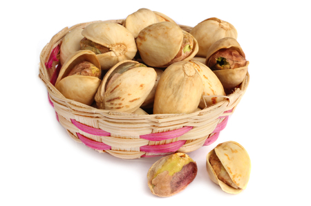 Roasted pistachio nuts isolated on bamboo basket. 写真素材