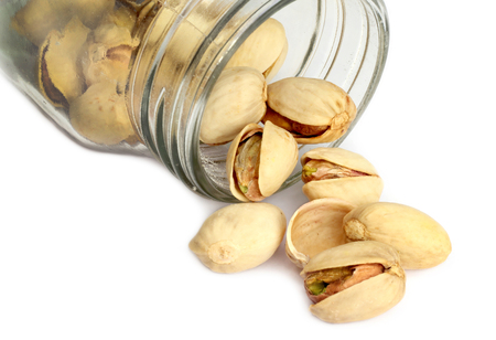 Roasted pistachio nuts isolated in a glass jar