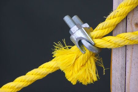 clamped: a yellow rope for a tie-down is clamped by metallic fastening