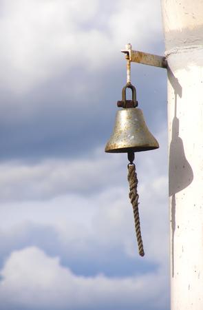 ferruginous: Ferruginous ship bell on a background cloudy sky