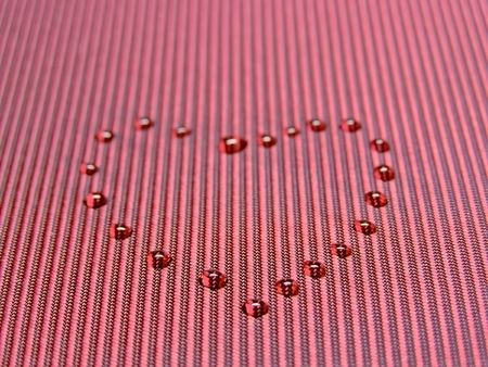 sprinkling: heart from water drops on the red fabric