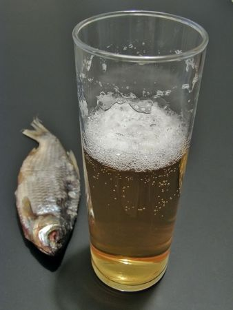 near beer: Dry fish near the glass of beer         Stock Photo