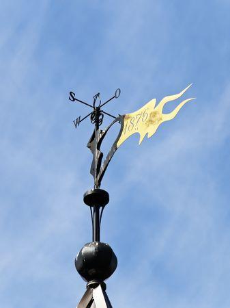 airflow: Metallic weather vane against the blue sky