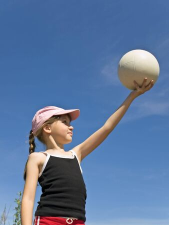 girl hold white ball against blue sky photo