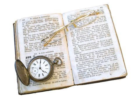 Isolated old open book with glasses and clock on it against the white background  photo