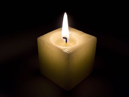 lit candle: Single burning candle in the dark night