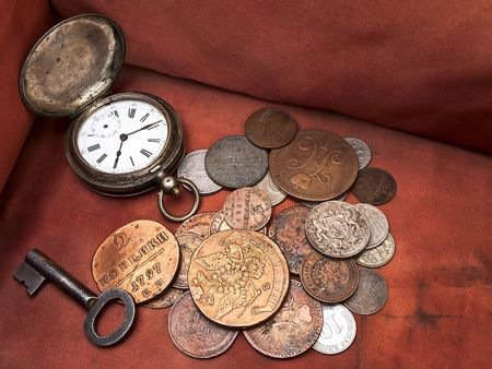 Old clock, key and coins in chest photo