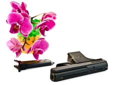 gun with pink orchid flower in glass at the background  photo