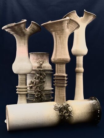 different ceramic vases over dark blue background photo