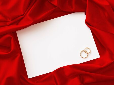 invitation card with two wedding rings and red cloth around photo