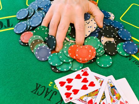 man hand on stack of chips at the green casino table near the cards